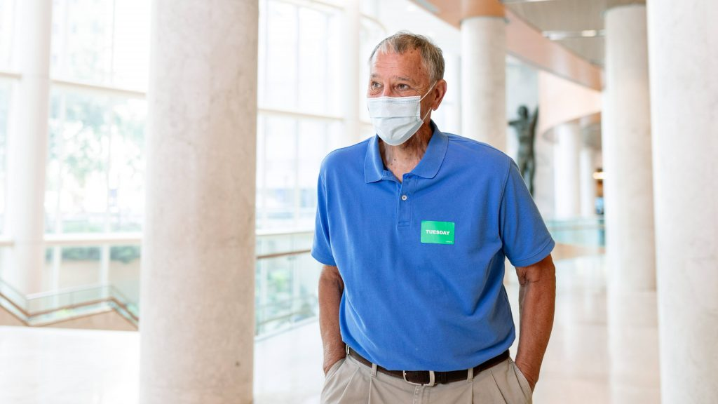 Mayo Clinic throat surgery patient James (Jim) Koski in a blue shirt and wearing a face mask while walking through the Gonda Lobby