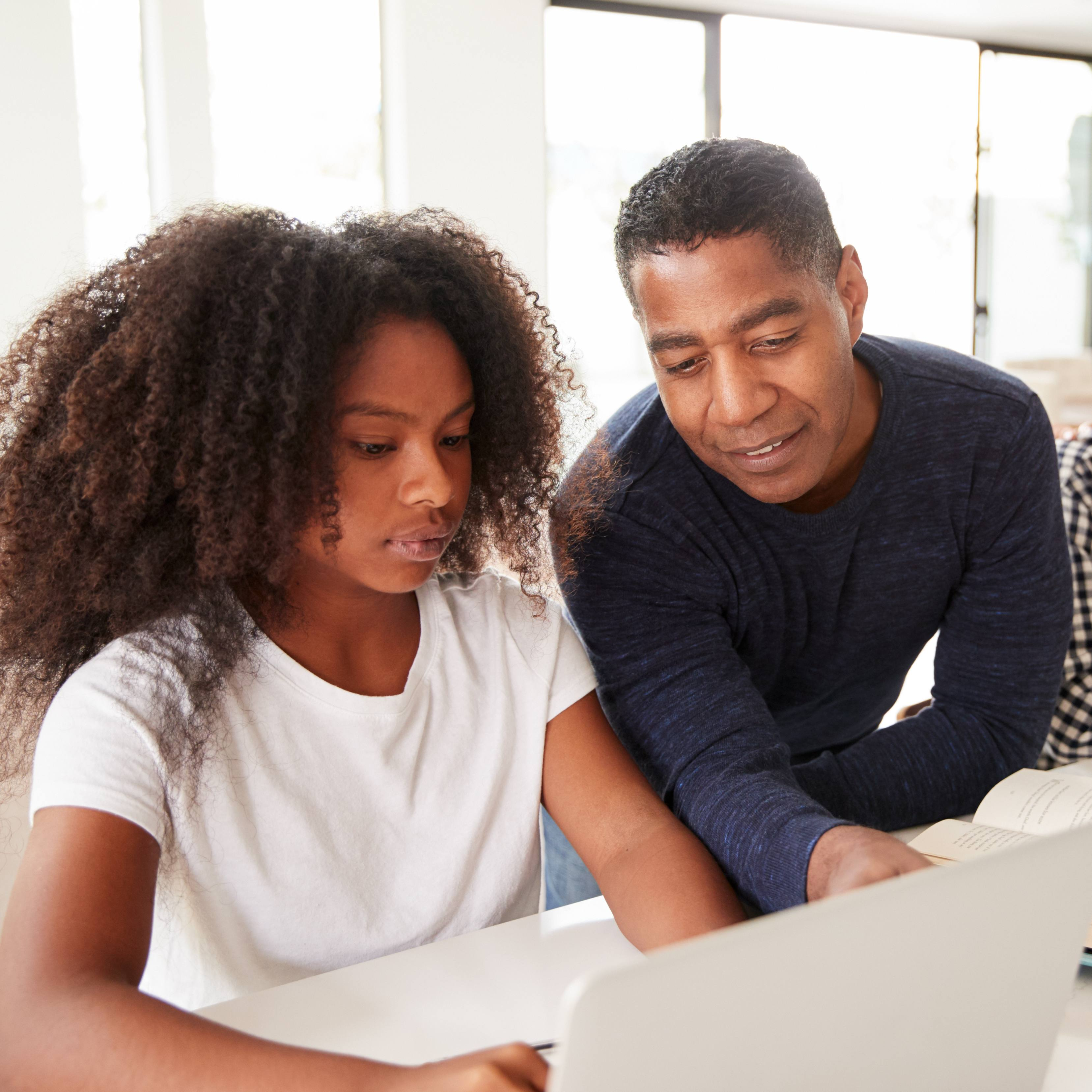 a Black teenage girls looking at a laptop computer with perhaps her father, a Black adult man, smiling and pointing to the screen to help her