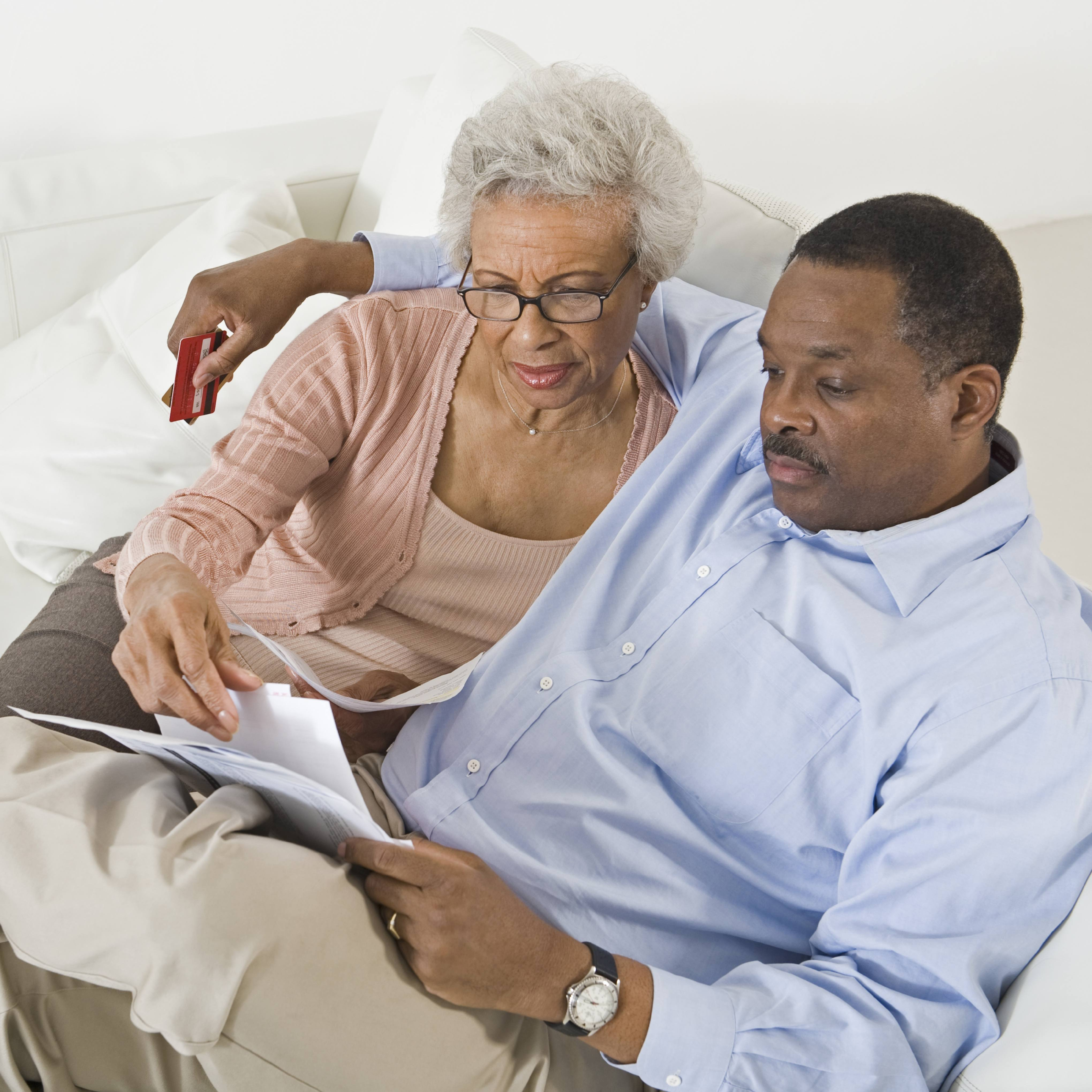 a Black woman and a Black, looking serious and thoughtful, sitting on a cream colored couch and reading paper documents together