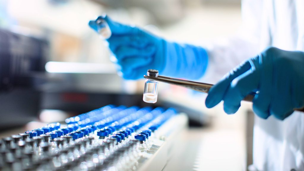 a Mayo Clinic lab technician wearing blue gloves, working with test tubes and regenerative medicine samples