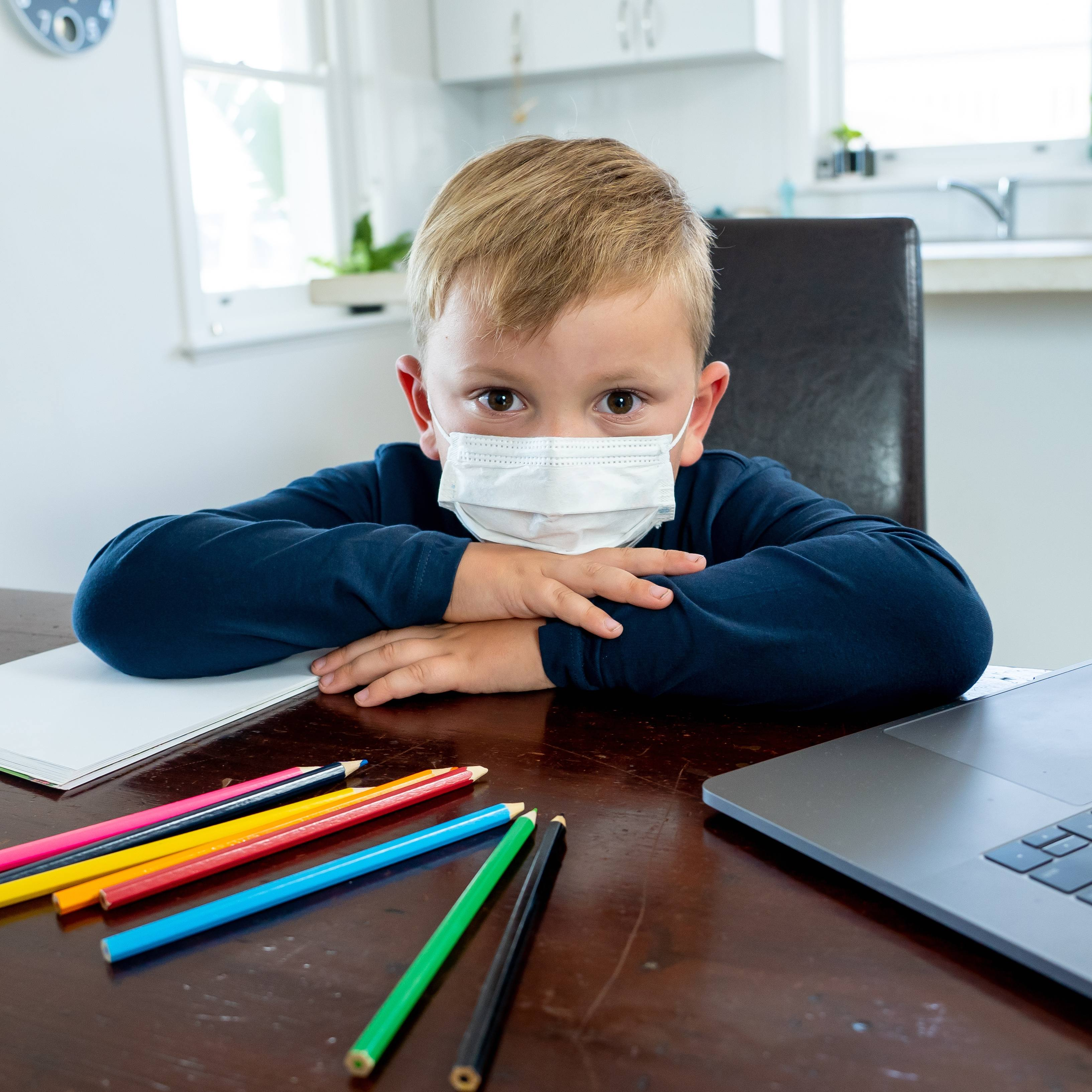 a young white school aged boy looking sad and lonely, wearing a face mask and sitting at a desk and resting his head on his arms, with paper, colored pencils and a laptop computer