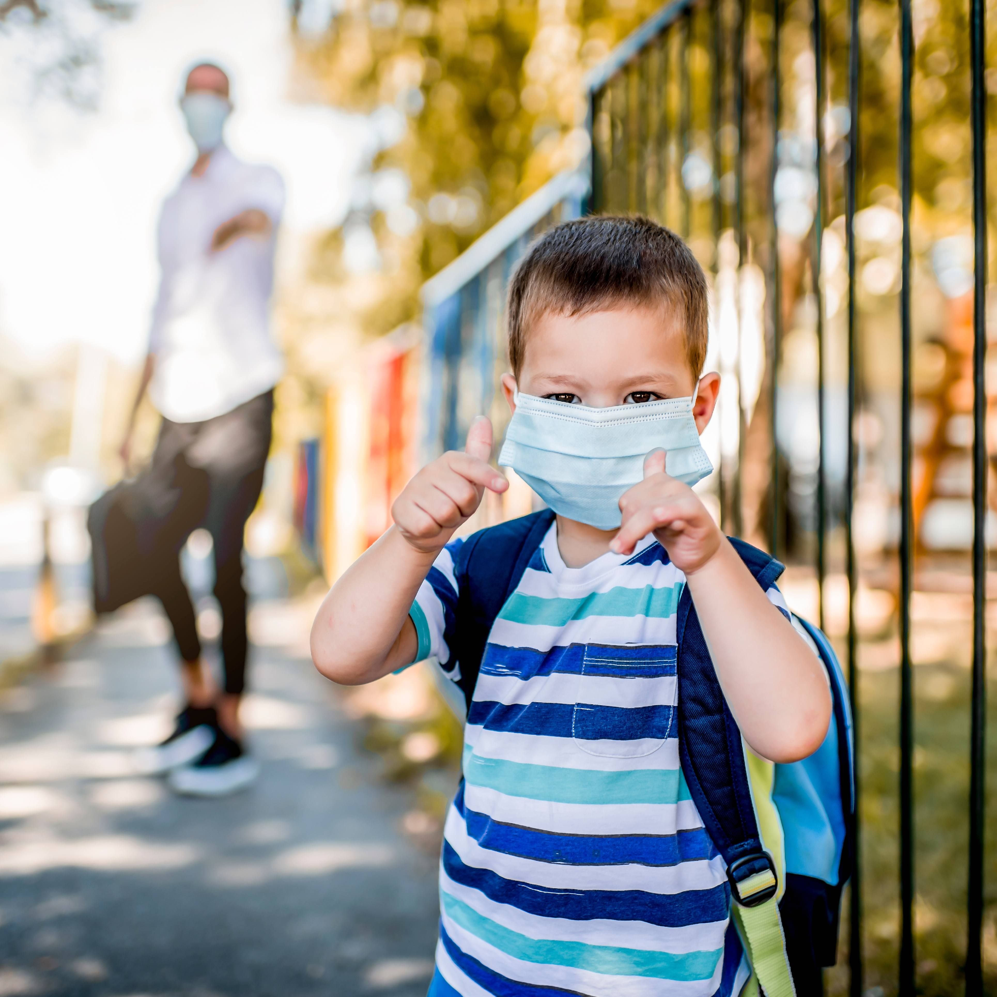 a little white pre-school or kindergarten aged boy in a striped shirt wearing a mask and carrying a backpack, getting ready to go into school