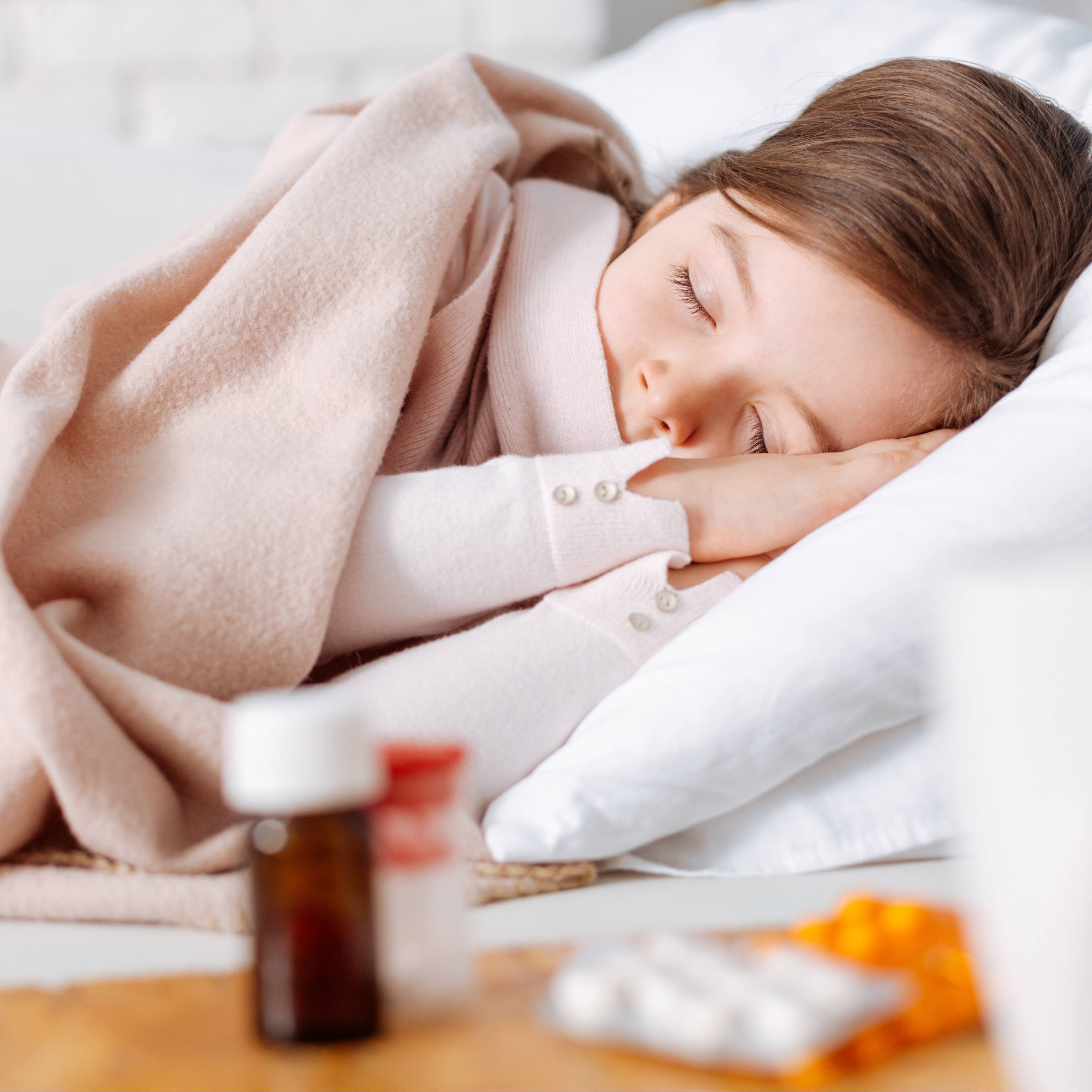 a little white school aged girl asleep in bed, covered in a blanket with medicine on a side table nearby, perhaps because she's sick and not feeling well with a cold or fever