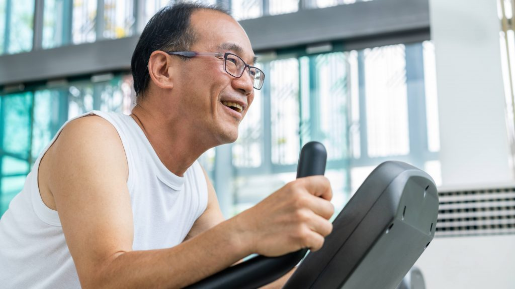 a middle aged Asian man wearing glasses and smiling while running and exercising on a treadmill