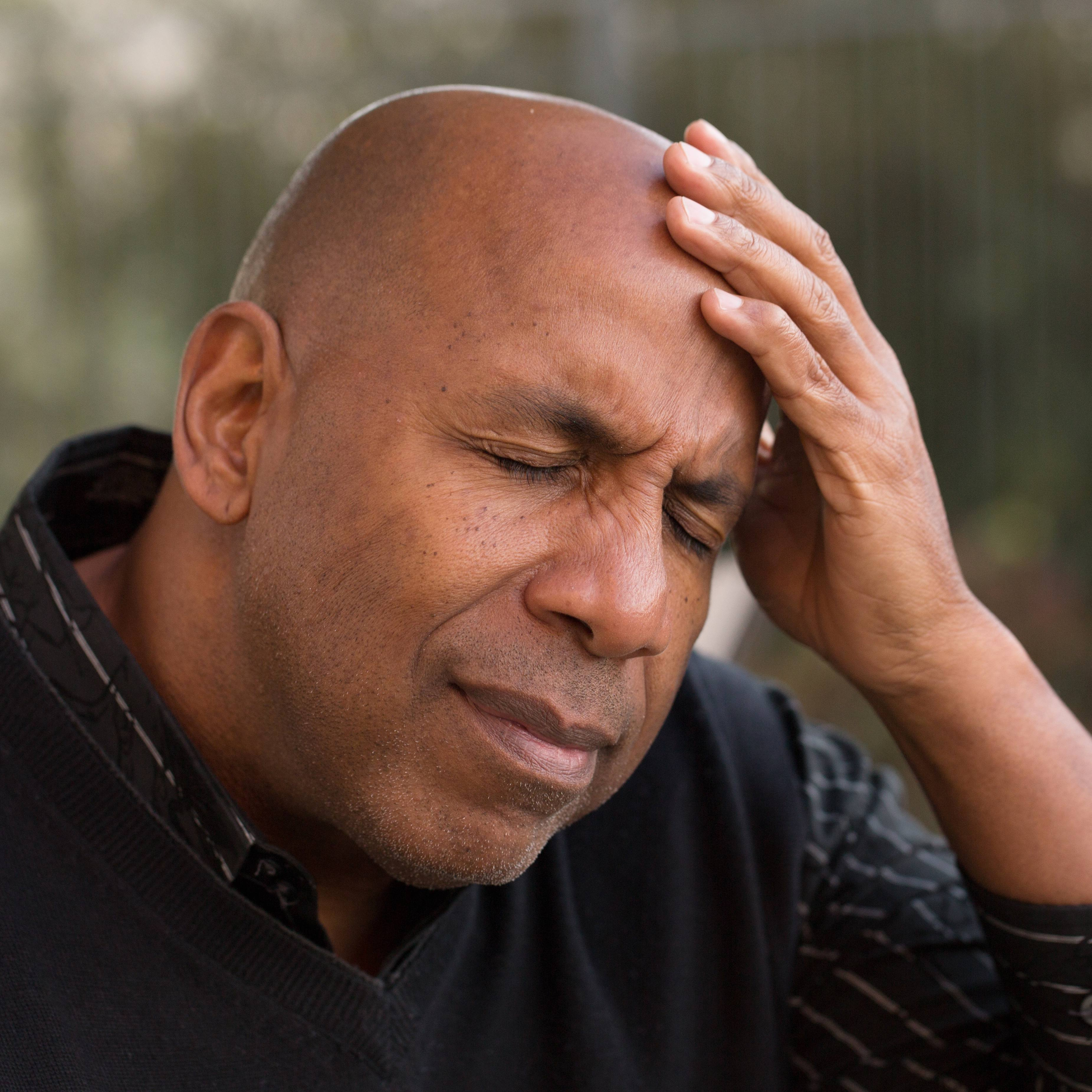a middle-aged Black man sitting outside, with his eyes closed and resting his head in his hand as if he's in pain, with a tension headache