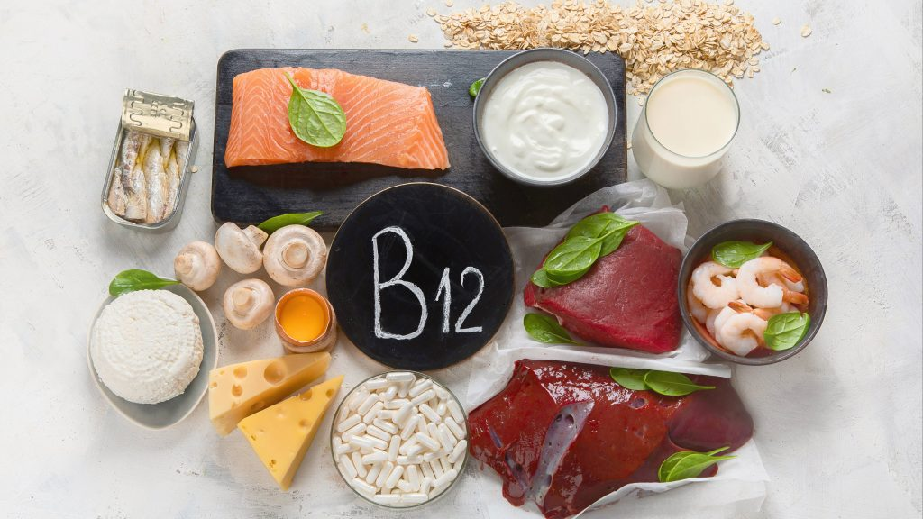 a table or kitchen counter top filled with vitamin B-12 supplements and foods like fish, cheese, mushrooms, milk