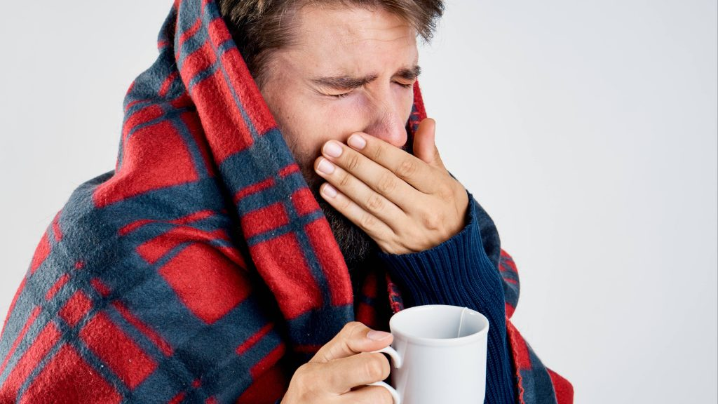 a young white man looking sick or cold, wrapped in a plaid blanket, holding a mug with tea and getting ready to sneeze or cough into his hand