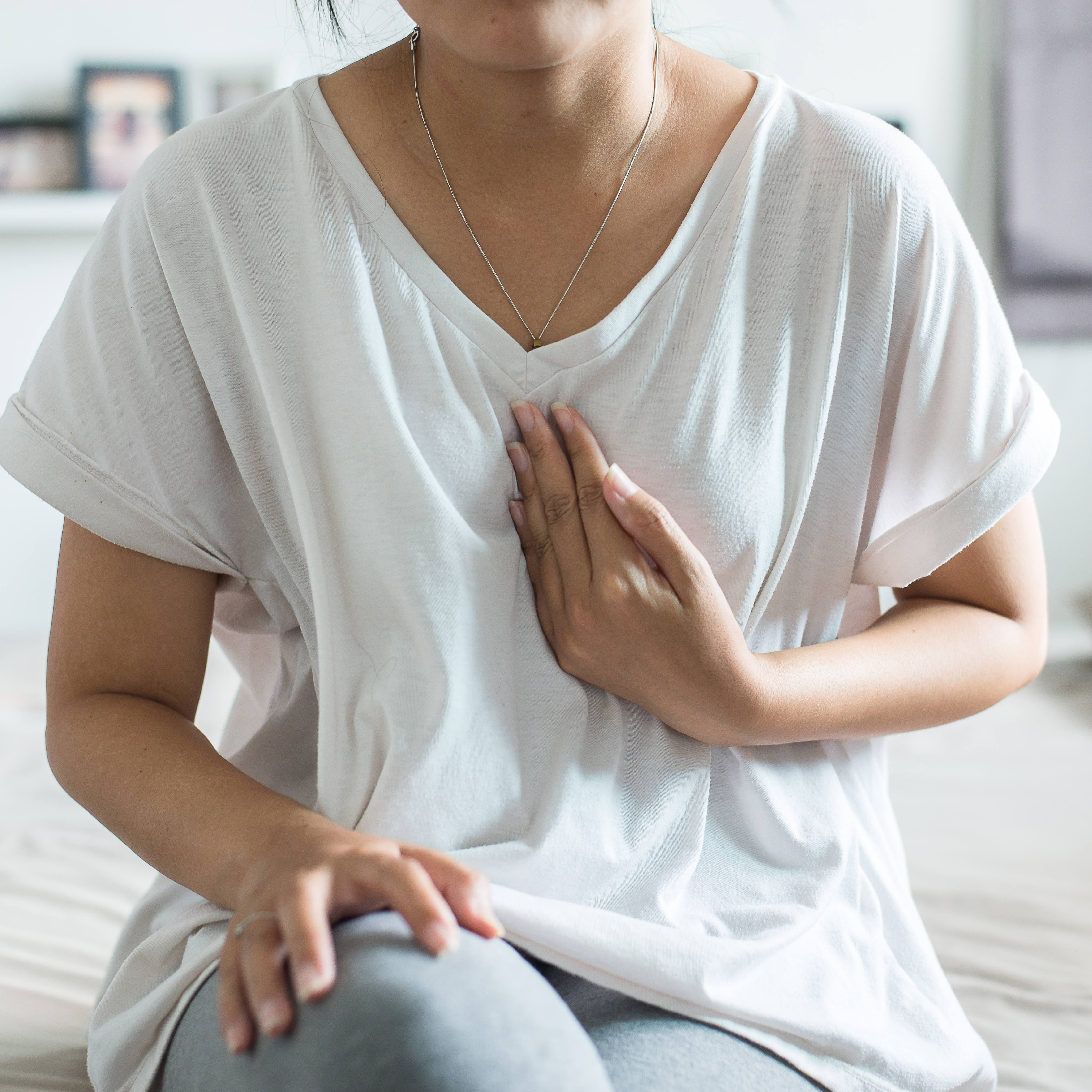 a white or perhaps a Latina woman in a white t-shirt sitting on the edge of bed, holding her hand to her chest, out of concern, stress, worry, heart pain