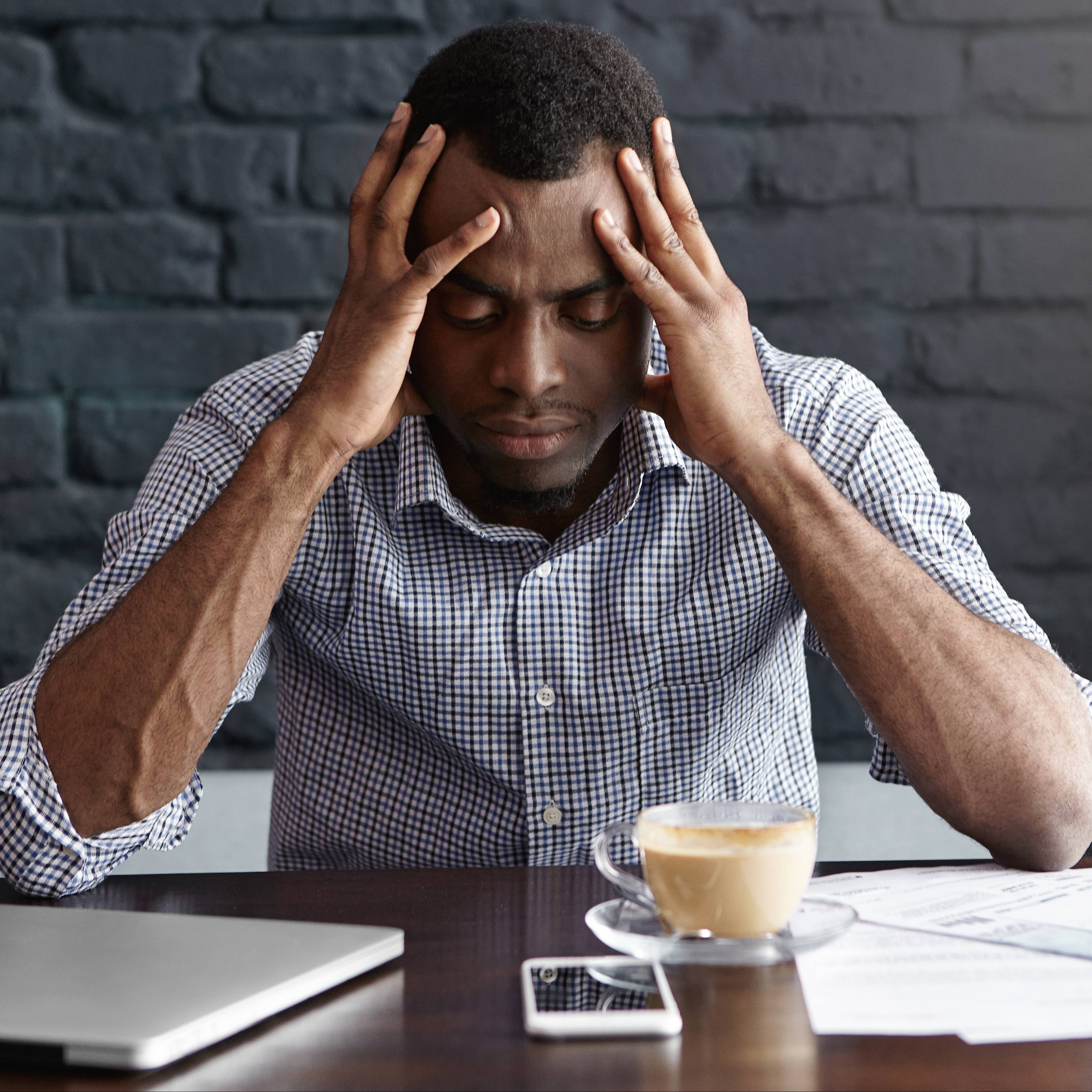a young Black man sitting at table with a coffee and a computer, looking stressed, worried, sad and holding his head with his hands, struggling with perhaps a headache