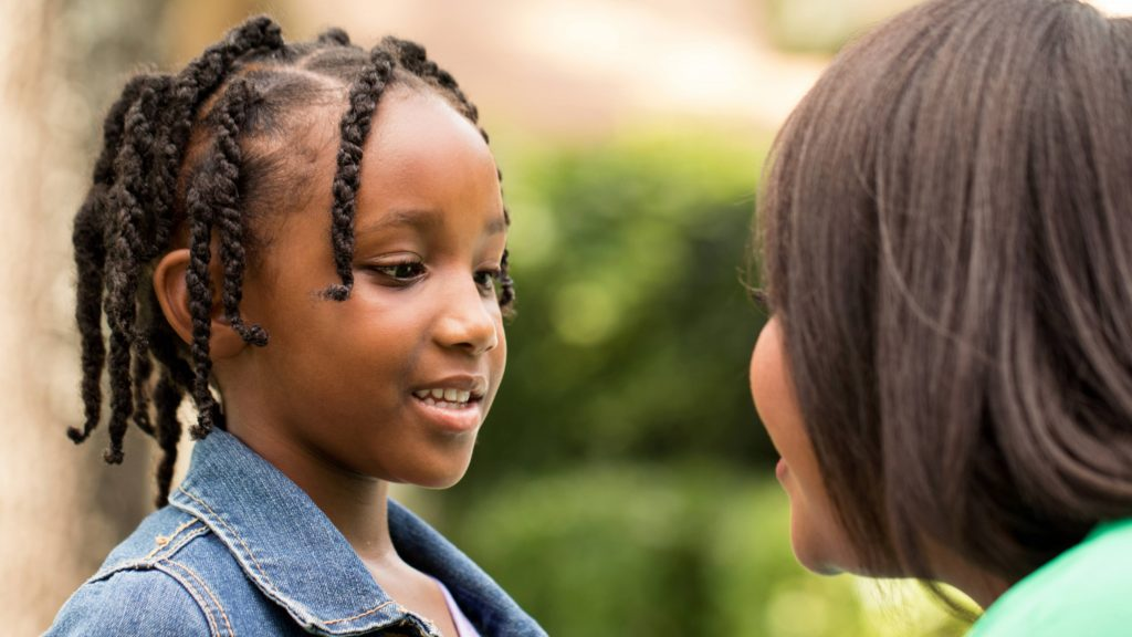 braids, smiling and talking to an adult woman, perhaps her mother or teacher