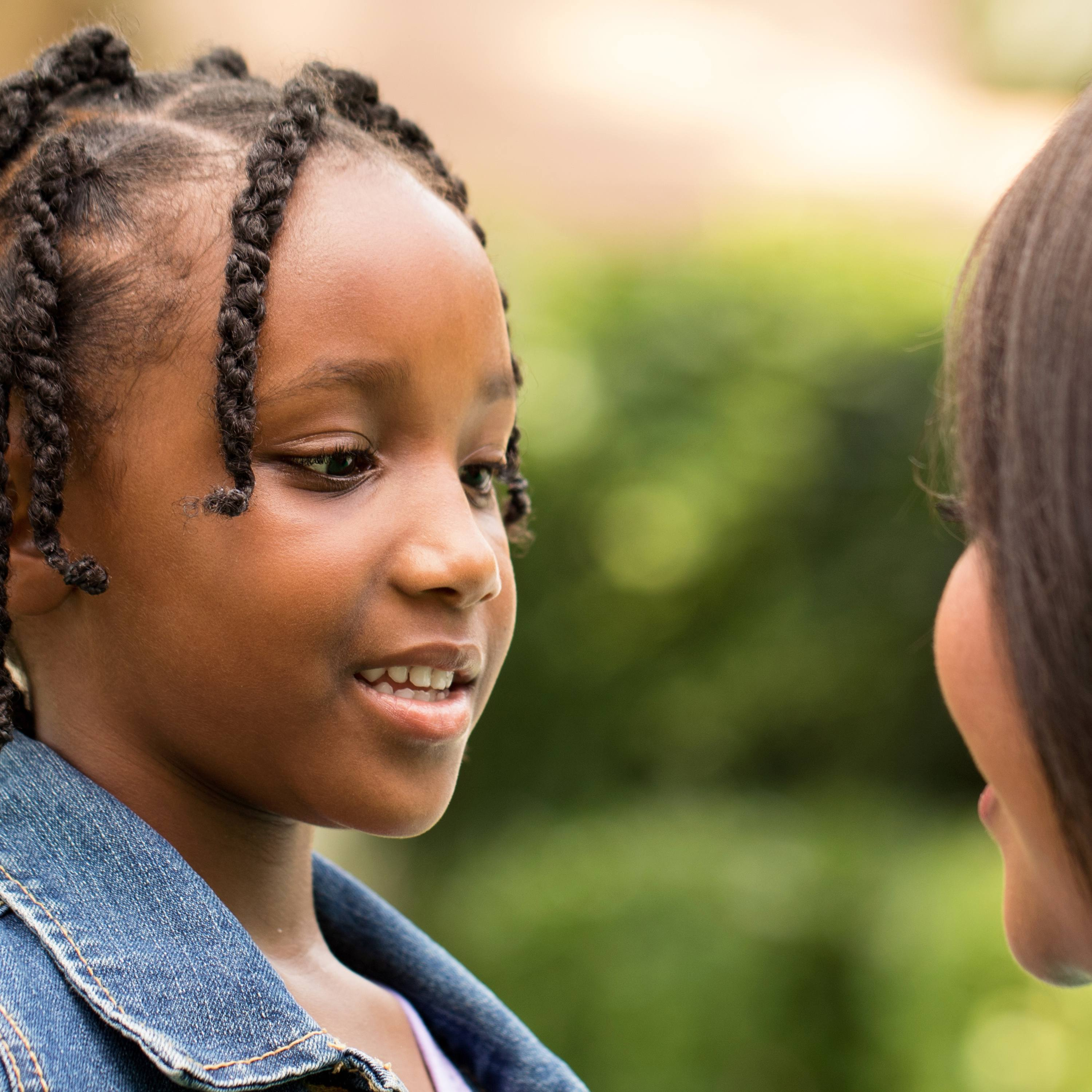 a young Black school-aged girl with African braids, smiling and talking to an adult woman, perhaps her mother or teacher