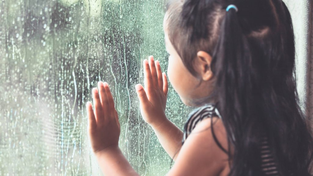 a young school aged perhaps Latina or Asian girl with ponytails, during a storm looking out a window with raindrops falling on the pane