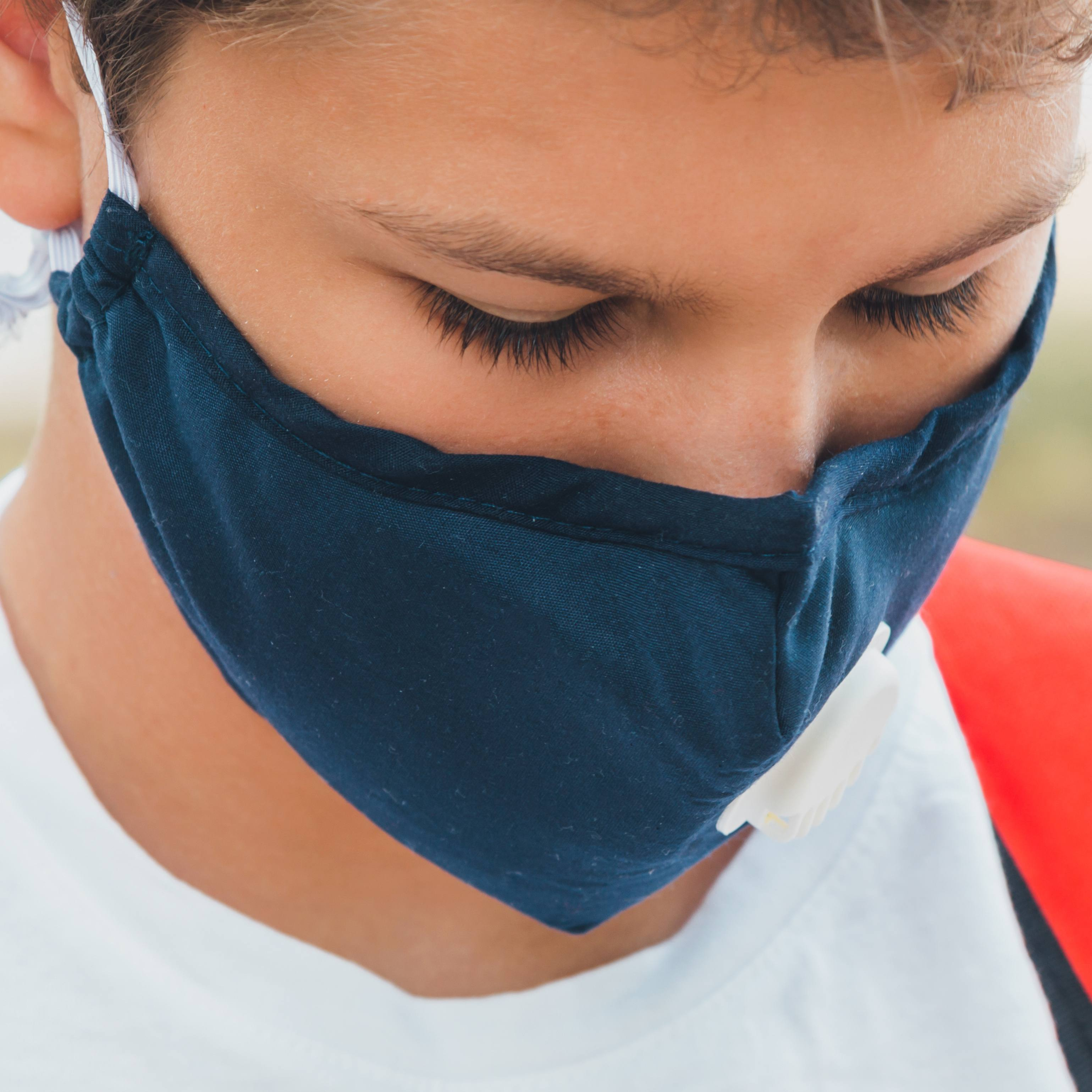 a young white adolescent boy wearing a face mask and carrying a school backpack
