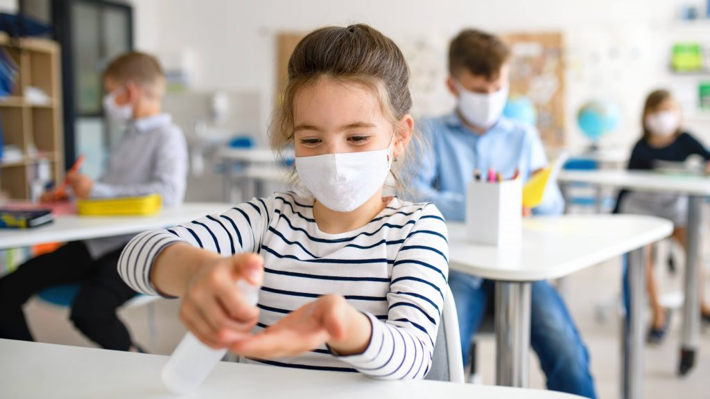 a young white girl in a school classroom, wearing a mask and putting sanitizer on her hands while sitting at her desk, social distancing from classmates