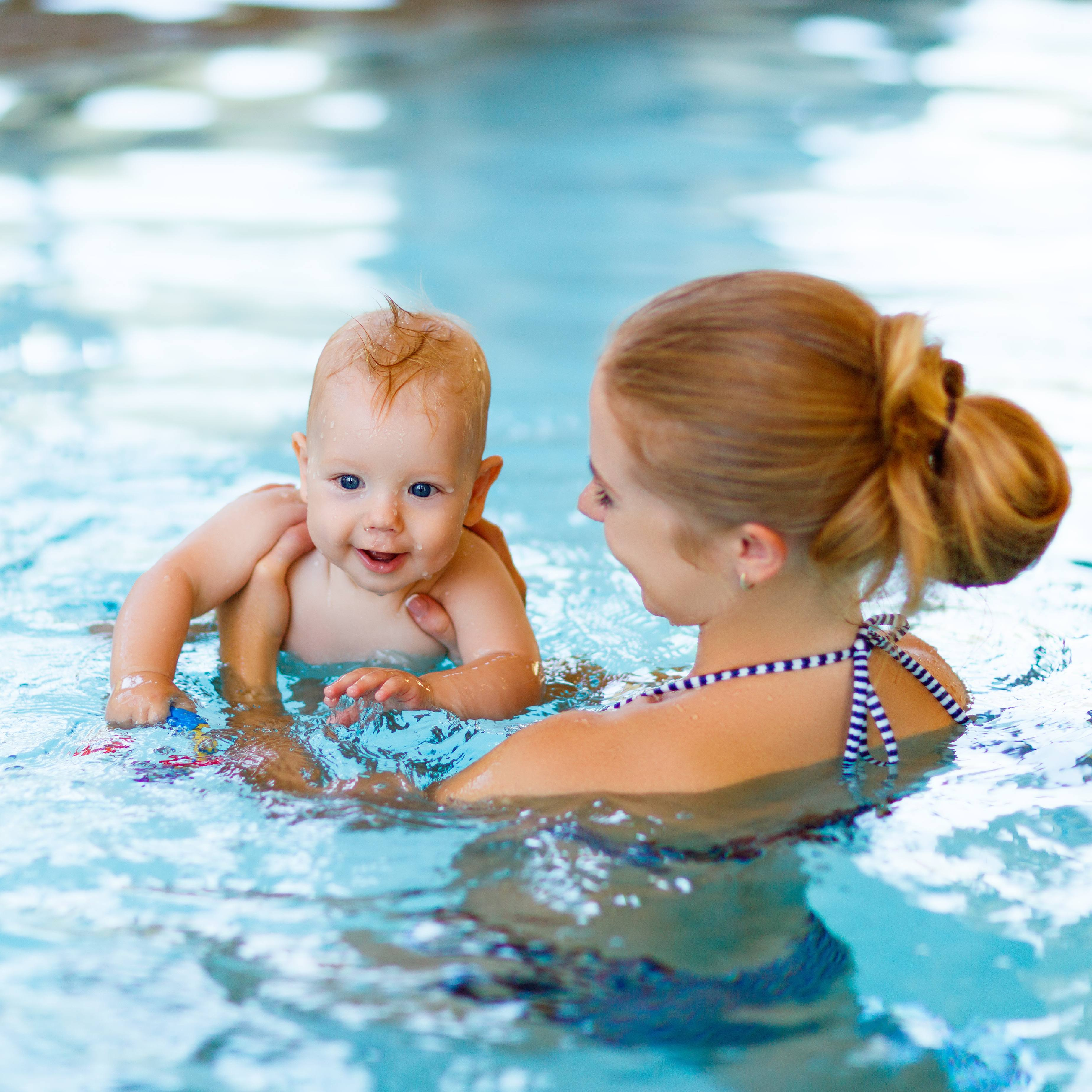 a young white woman in a swimming pool holding a smiling white baby in the water, learning to swim