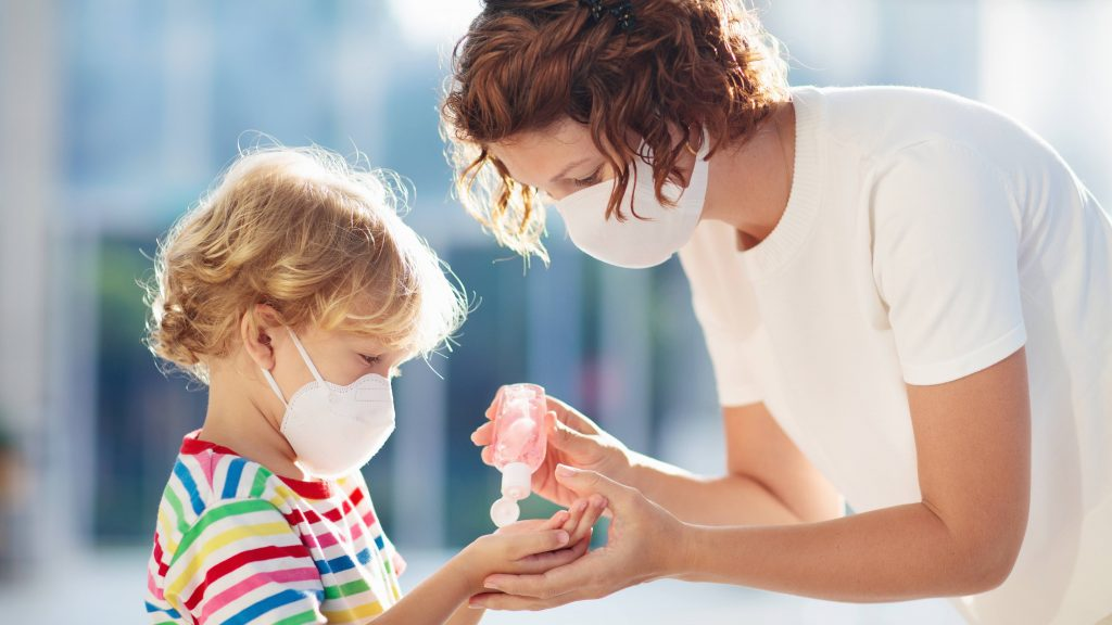 an adult white woman wearing a mask and putting hand sanitizer in the hands of a young white child who is also wearing a mask