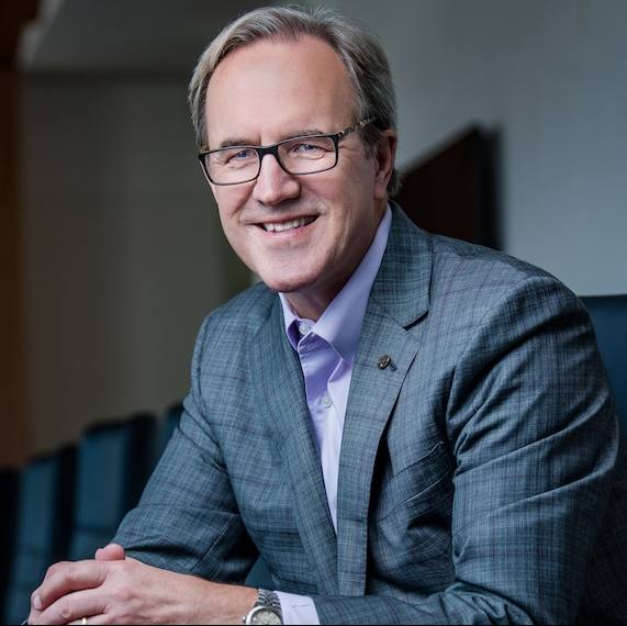 environmental picture of Ecolab CEO Douglas M. Baker, Jr., in a business suit, wearing glasses and smiling