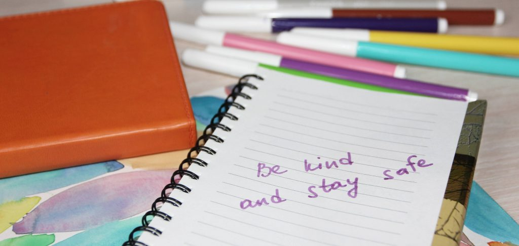 different colored writing markers with a school notebook and the words 'be kind and stay safe' written on the paper