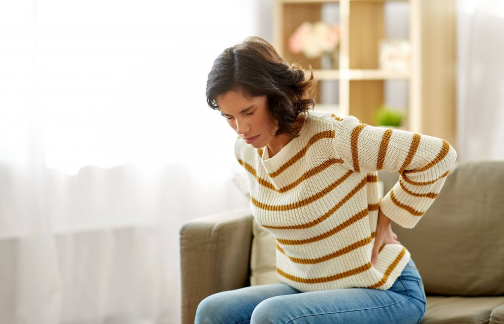 a young white woman in a striped sweater, sitting on a couch, wincing in pain, her eyes closed, looking sad and holding her back because it hurts