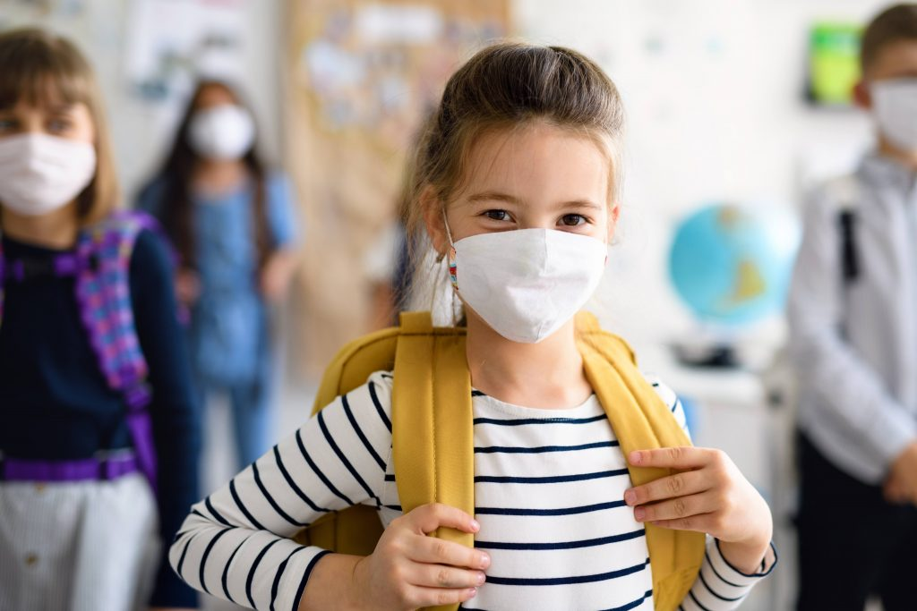 a young white schoolgirl in a classroom wearing a backpack, with other students all wearing masks and social distancing