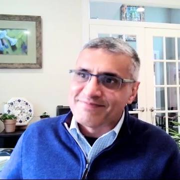 Dr. Goyal wearing a blue sweater and glasses, doing a Zoom interview from his dining room