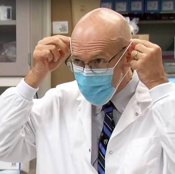 Dr. Gregory Poland in a white lab coat and putting on a blue face mask