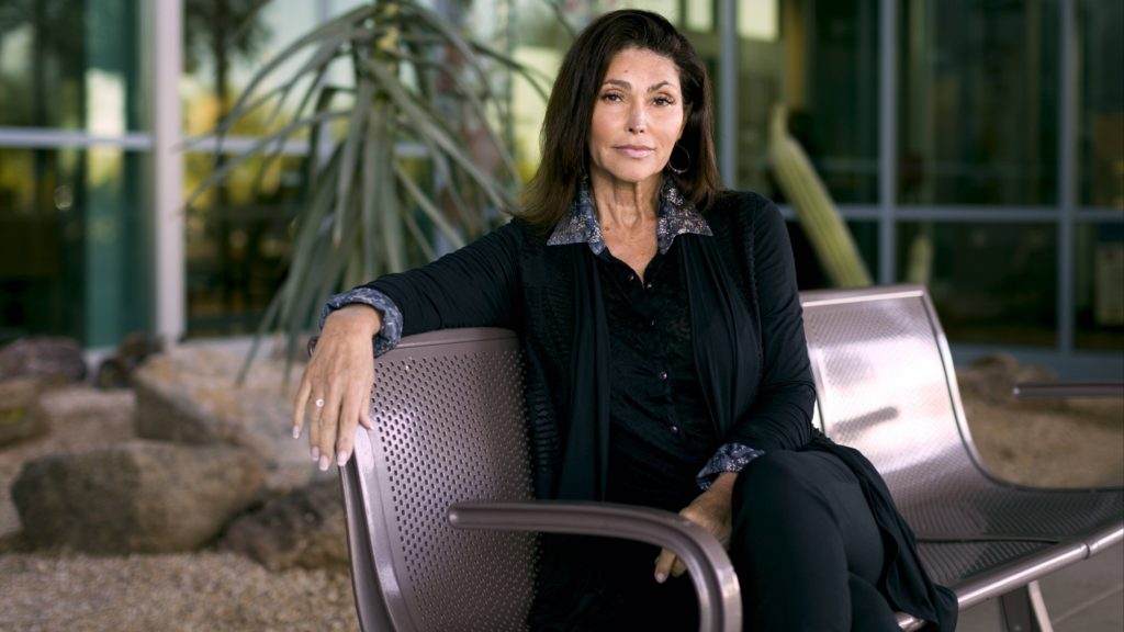 Mayo Clinic cancer patient Sabrina Falcon in a black pantsuit sitting on a bench outside with rocks and palm branches in the background