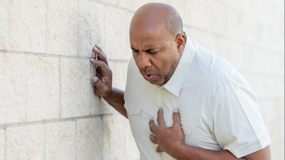 a Black middle aged man in a white shirt holding his hand to his chest and leaning against a wall in pain, short of breath and perhaps having a heart attack