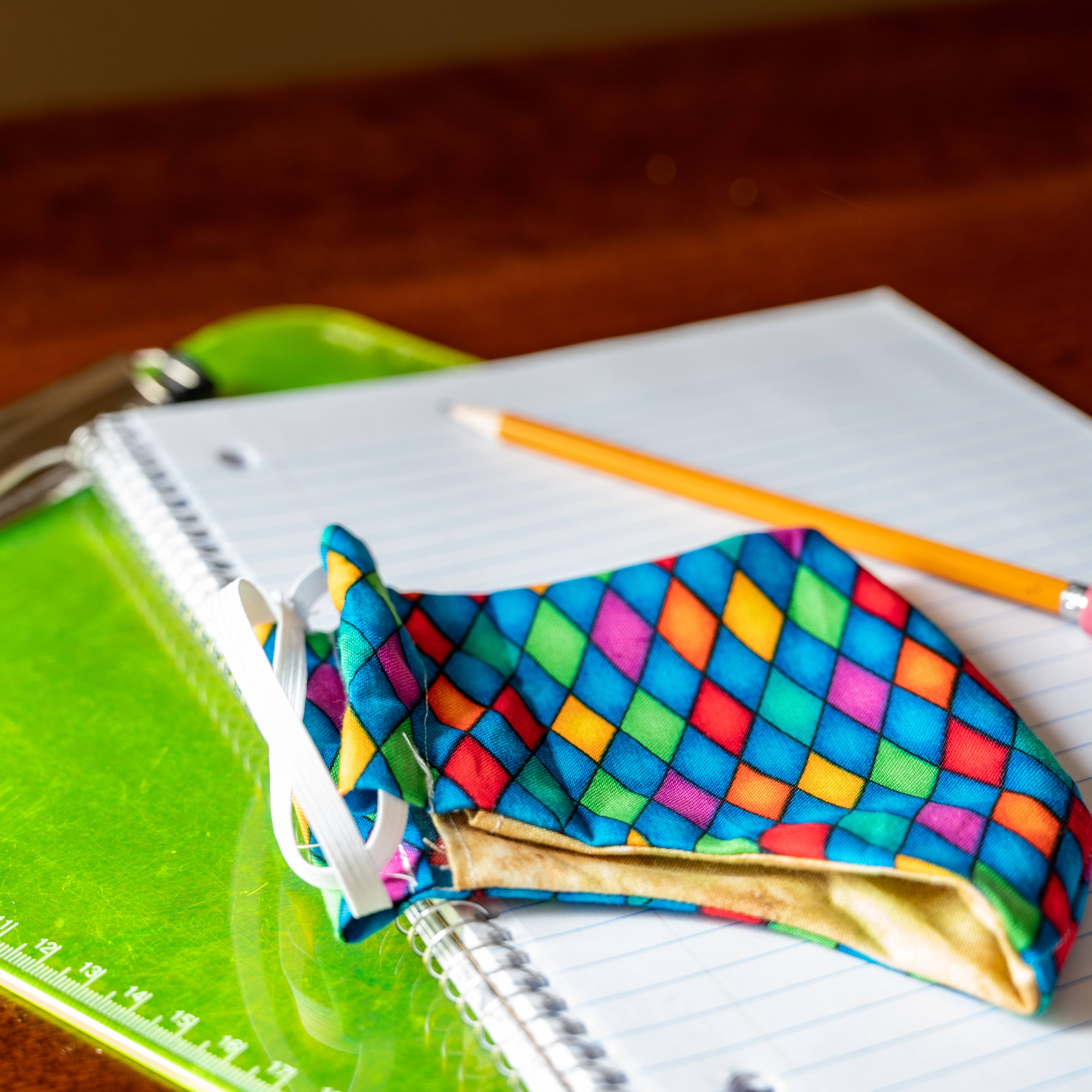 a clipboard, school notebook, pencil and colorful face mask on a wooden table