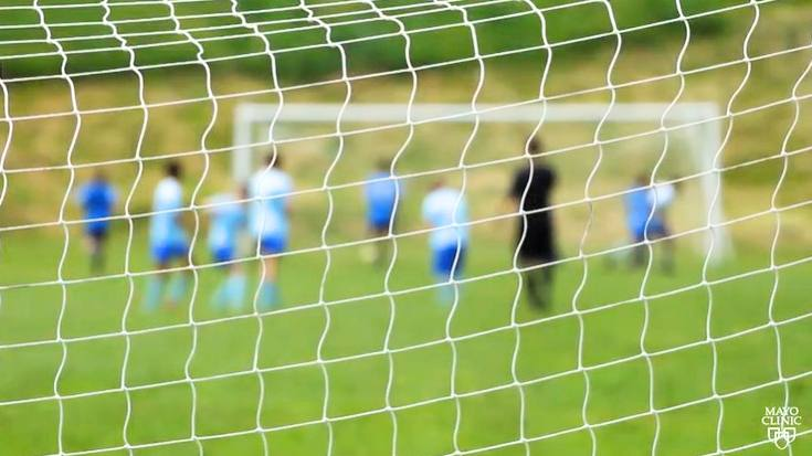 a green soccer field with a goal net in the foreground and young players in blue uniforms playing in the background