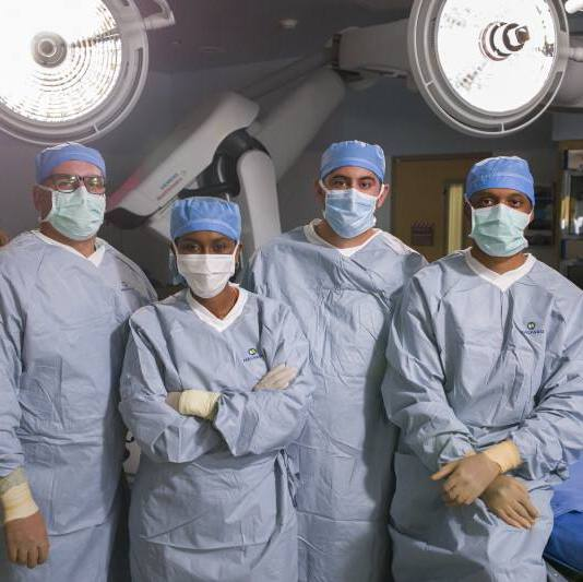 a group of diversity Mayo Clinic medical staff in surgical gowns, face masks and gloves, PPE, standing together in an operating room