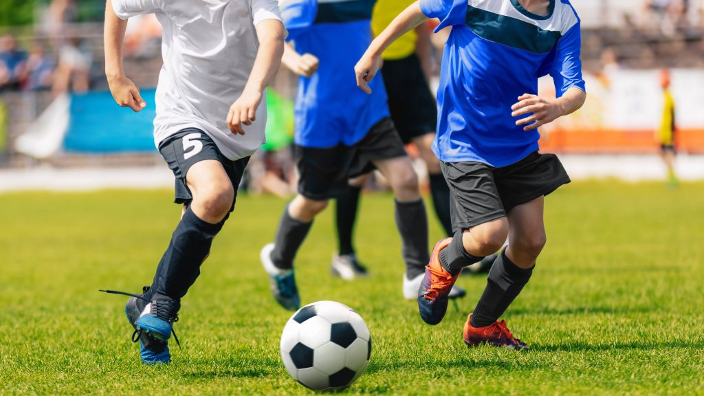 Un grupo de jóvenes adolescentes con uniformes azules y blancos jugando al fútbol en un campo verde