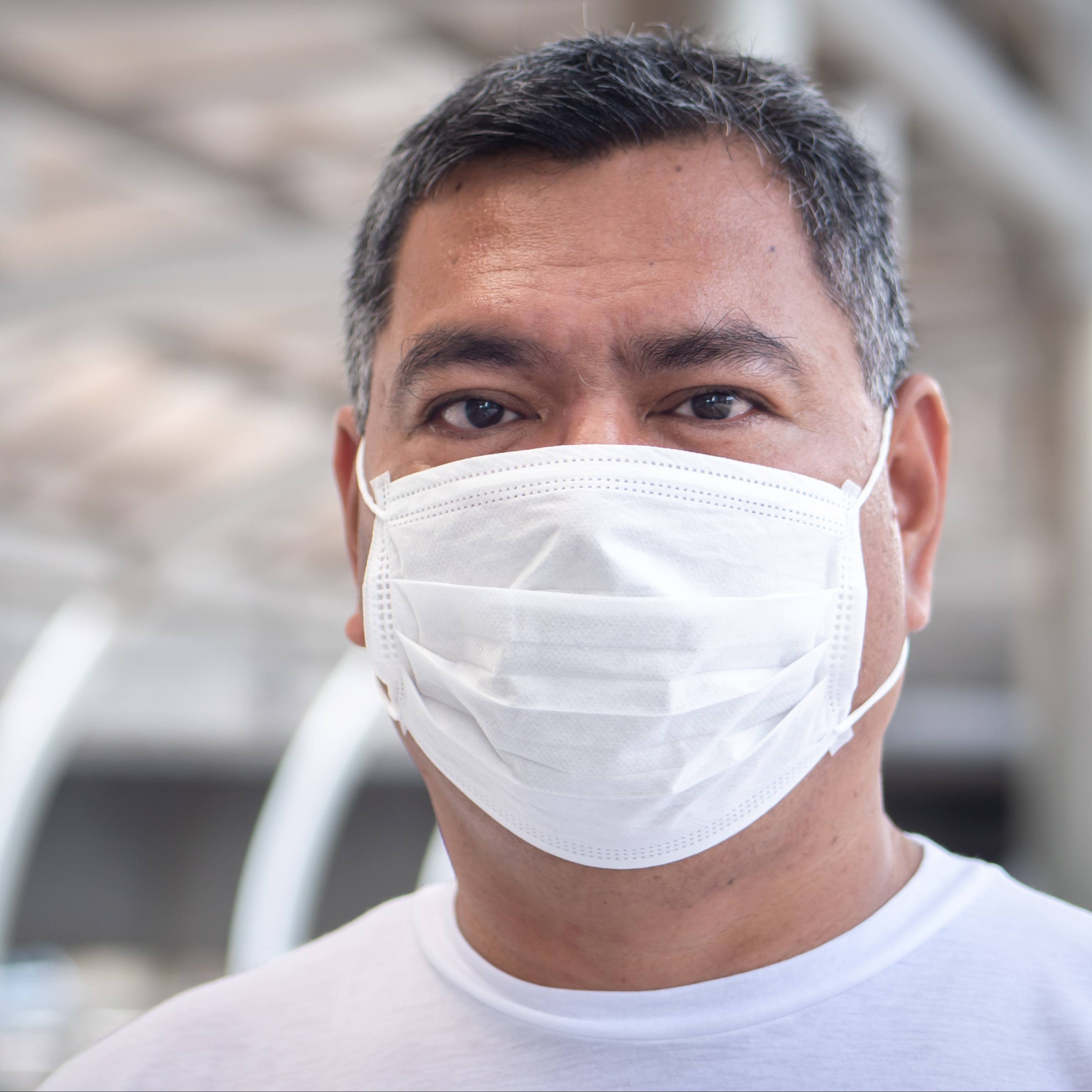 a middle aged man, perhaps Latino, with black and gray hair and wearing a white mask
