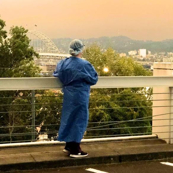 an Oregon healthcare worker in blue scrubs standing on a rooftop, bridge or perhaps hospital parking lot looking out at the wildfire smoke covering the city and hills