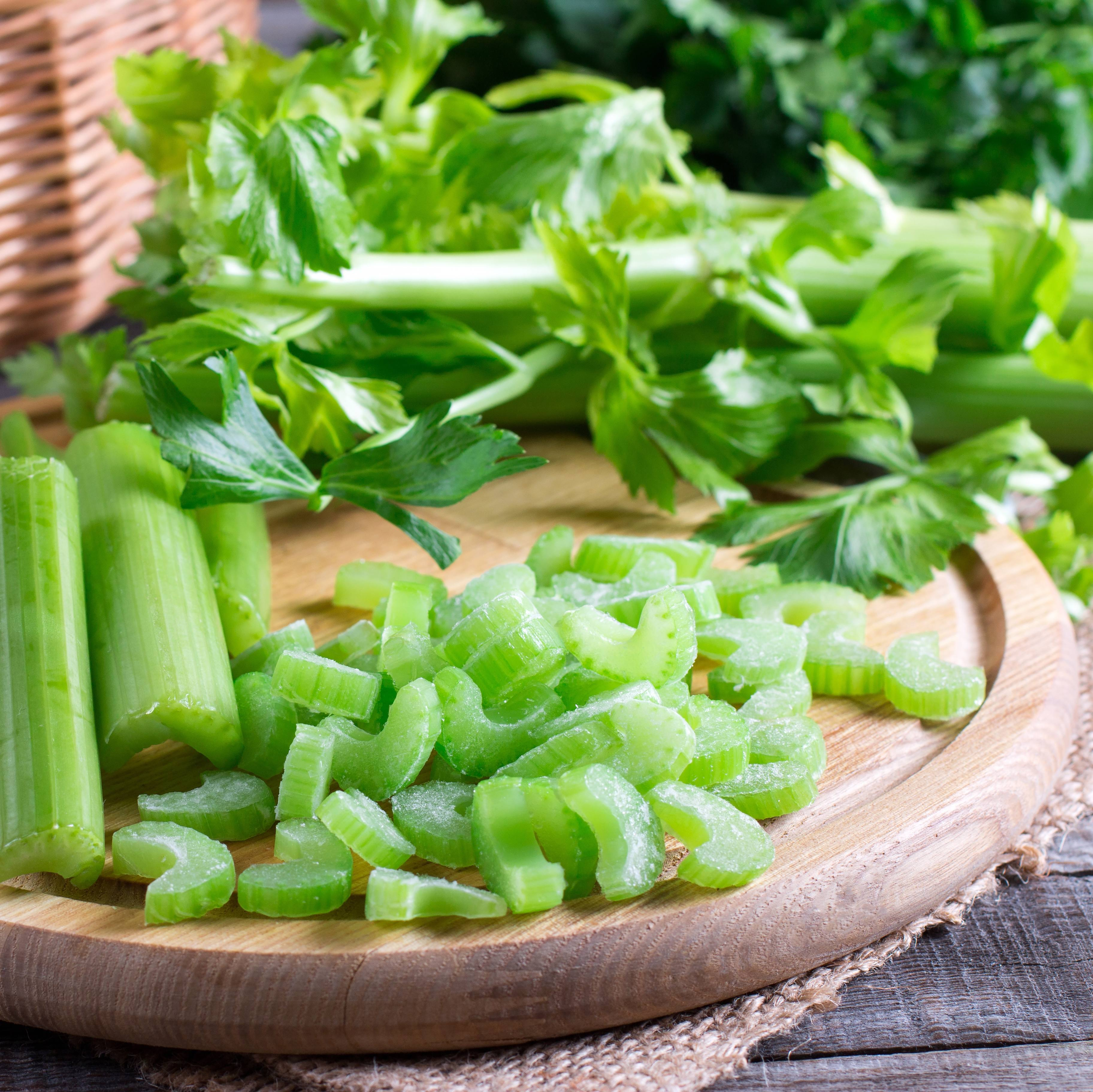 chopped up stalks of celerey on a wooden platter, perhaps on a kitchen table with other vegetables