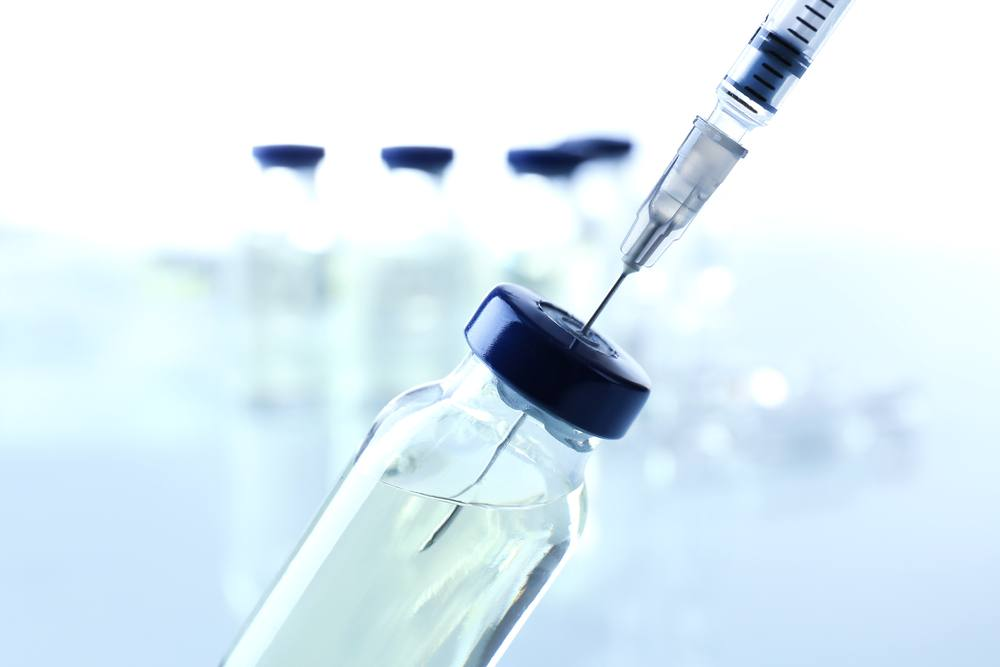 a laboratory vile or tube in a research lab with liquid in it and a needle or syringe withdrawing liquid, perhaps medicine or a vaccine
