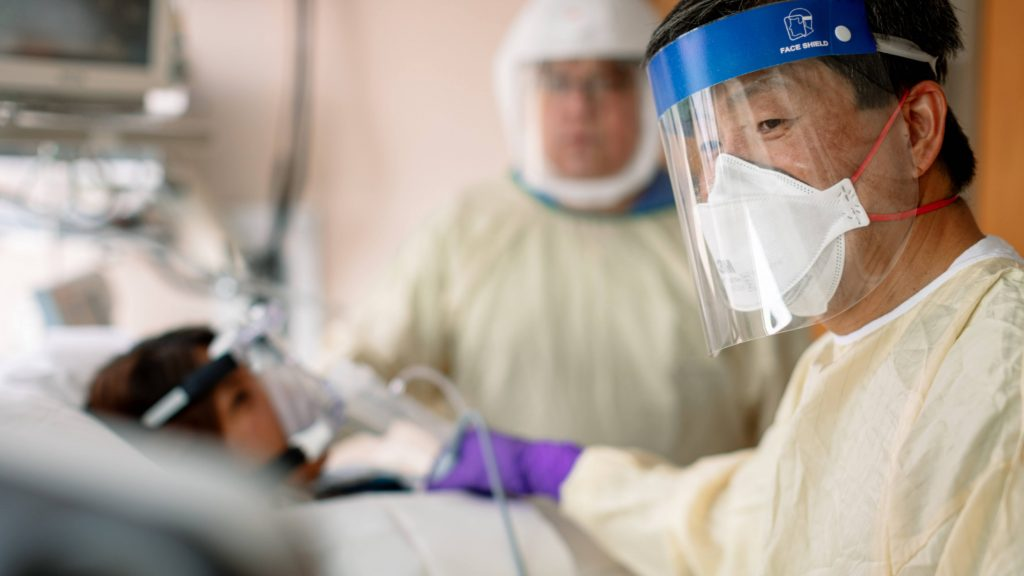 Mayo Clinic Intensive Care Unit medical personnel wearing PPE, personal protective equipment, helping a COVID-19 patient breathe on a ventilator in the ICU