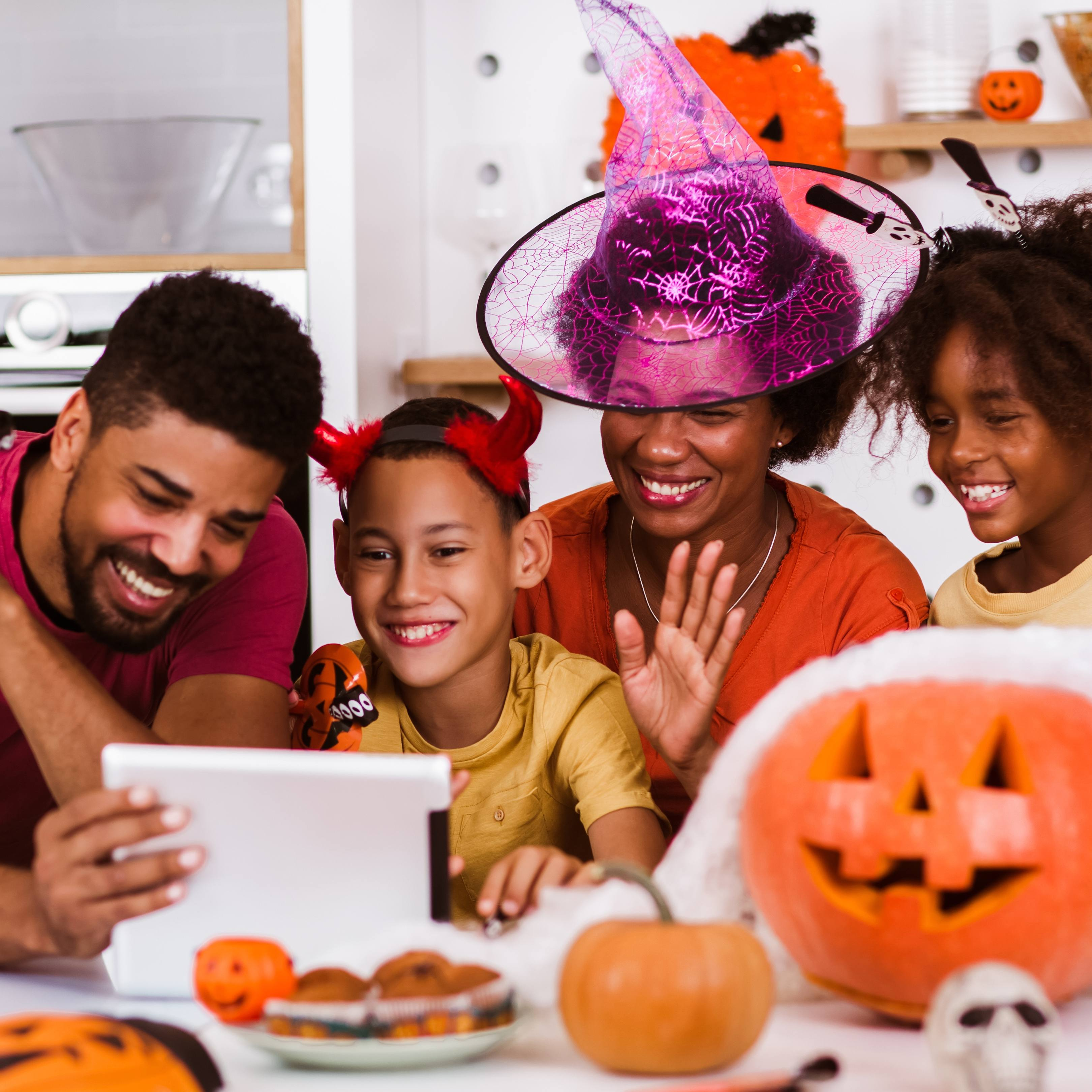 a Black man and woman, perhaps parents, with two children laughing and smiling while having fun with Halloween decorating activities