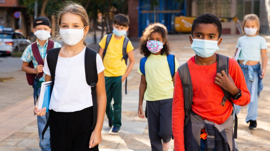 a diverse group of school aged children, tweens, wearing face masks and carrying backpacks, walking together with several feet between them
