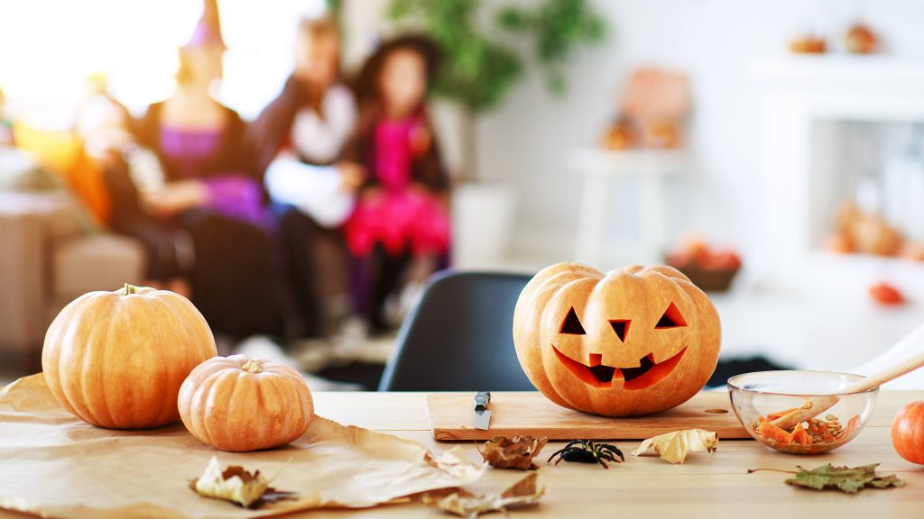 a table with Halloween pumklins and leaves, with children (out of focus) in the backgound in costumes