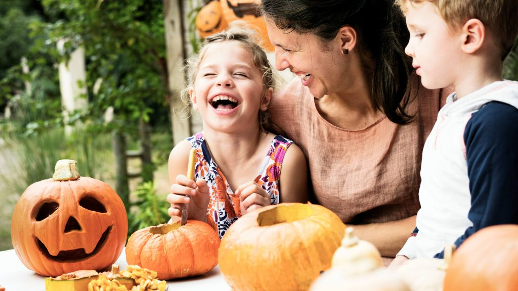 a white adult woman, maybe a mom, laughing and smilng with two white children as they make Halloween arts and craft activities