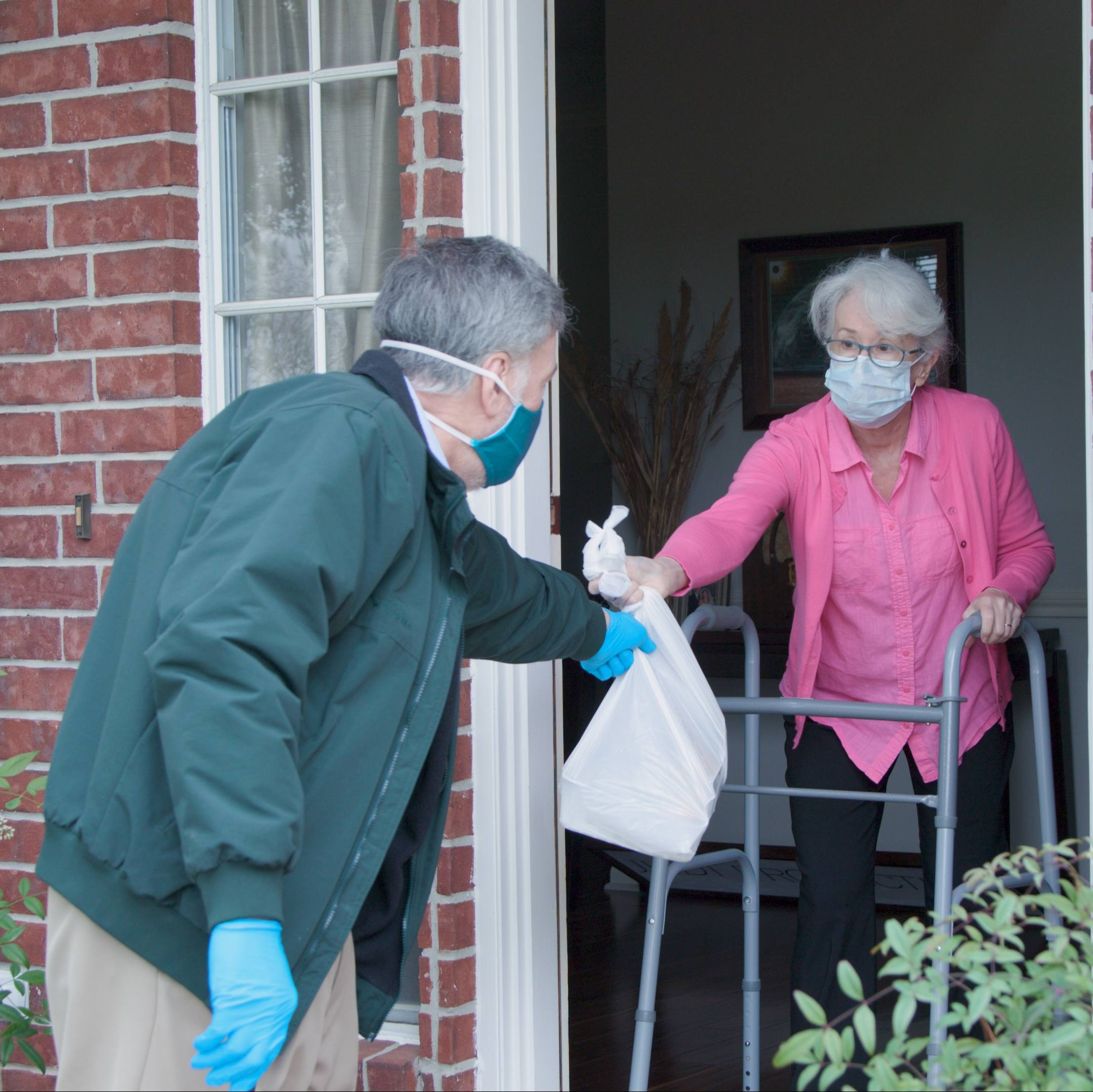 a white middle aged man wearing a mask and gloves delievering food to an older white woman, also wearing a mask, at her front door during COVID-19 pandemic