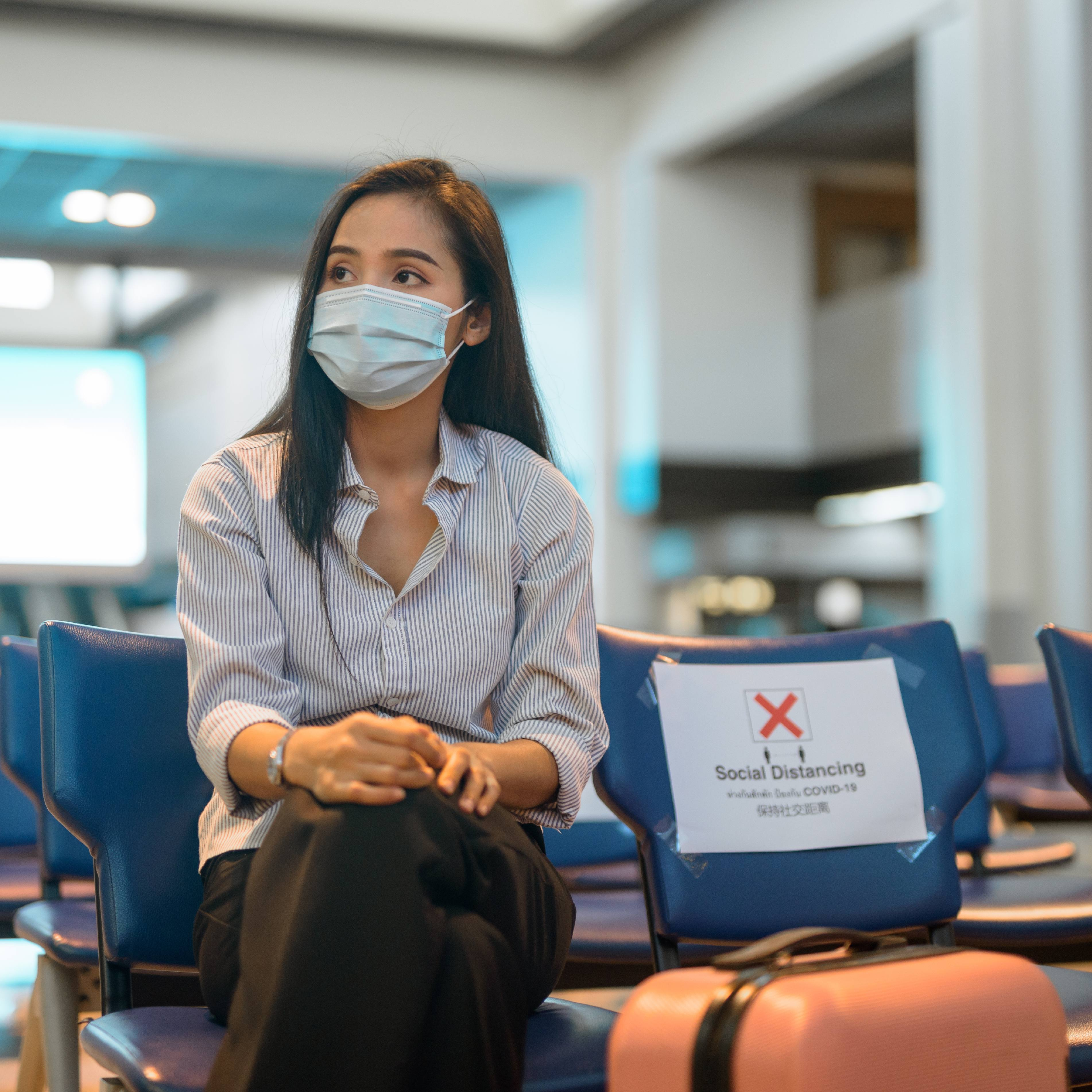 a young adult woman, perhaps Asian or Latina, sitting in an airport with a suitcase and social distancing COVID-19 signs on the seats