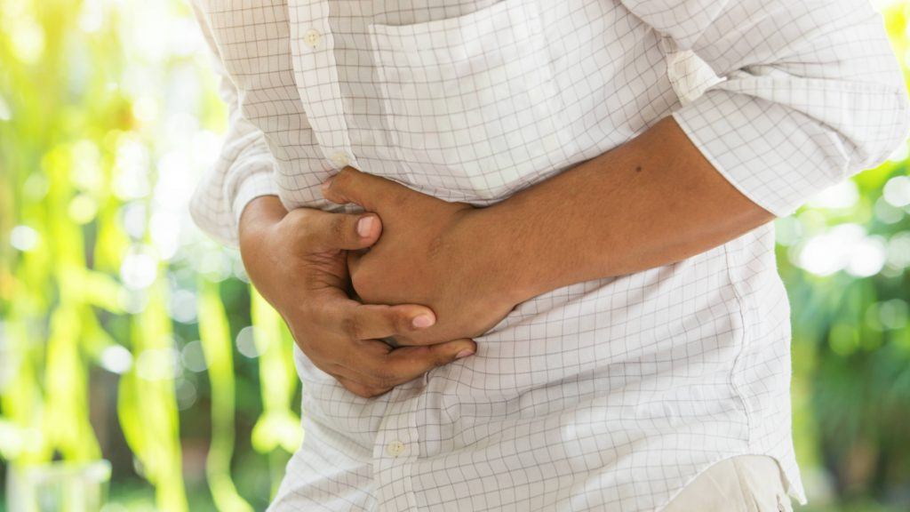a young man, perhaps Latino, crossed his arms around his stomach in pain