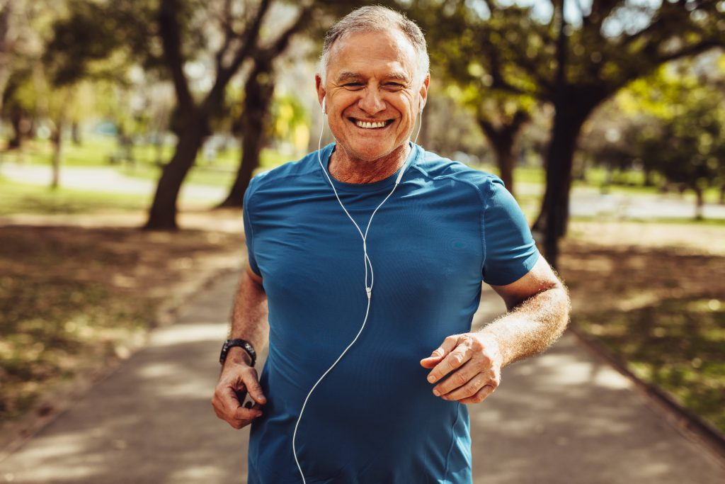 a smiling older man out for a run on a sunny day, wearing earbuds