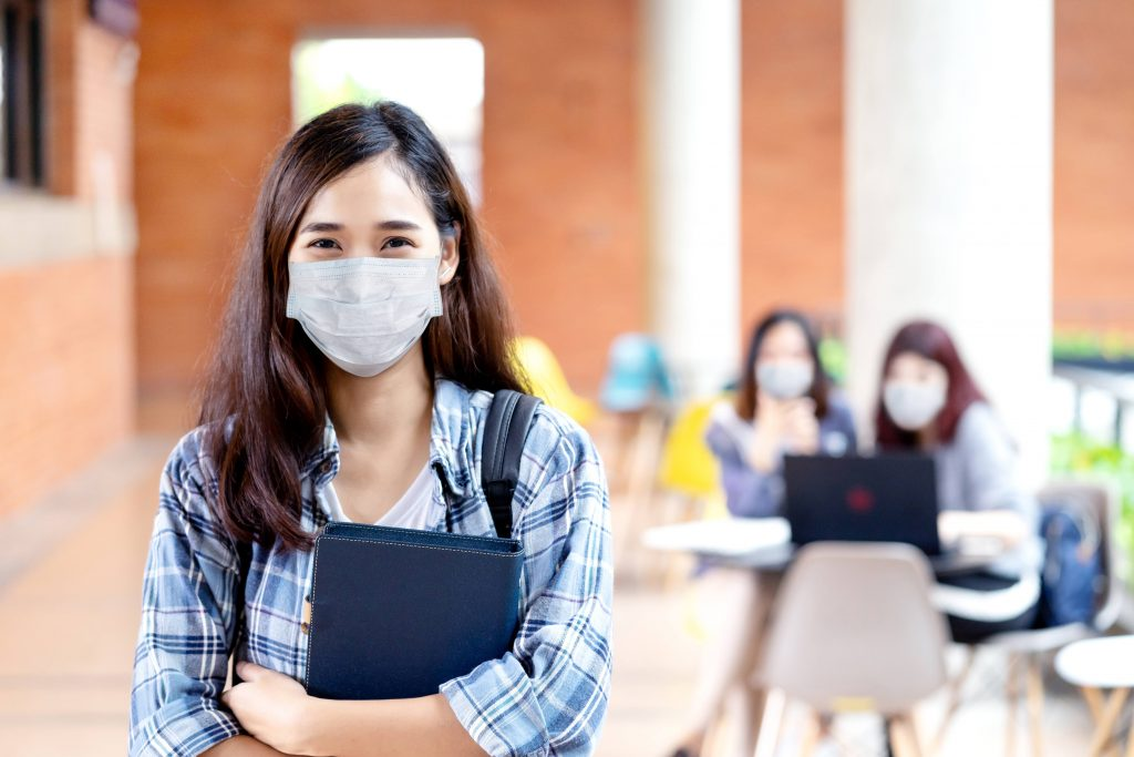 a young white, perhaps Asian, teenage girl wearing a face mask and holding a high school or college planner book