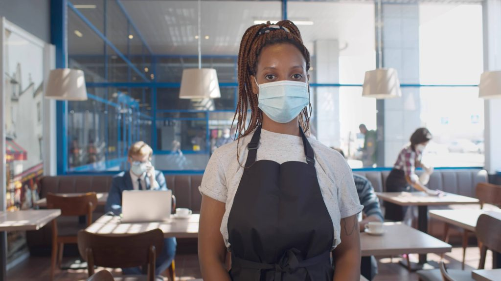 a young Black woman wearing a face mask and a work apron as a waitress in a restaurant