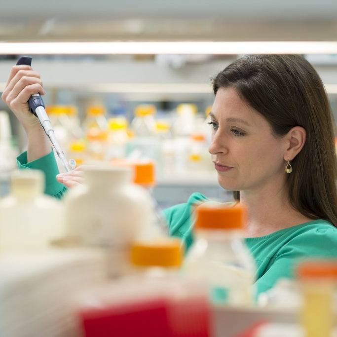 Dr. Tania Gendron in a research lab working measuring liquids
