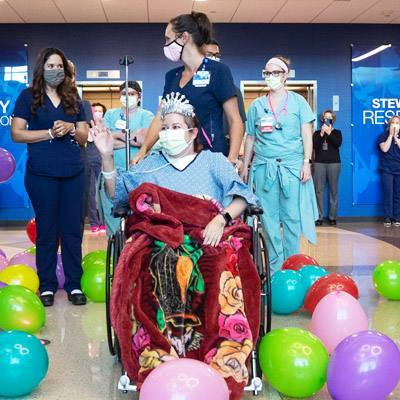 Arizona COVID-19 patient Reyna Lopez in a wheelchair in a balloon-filled lobby with Mayo Clinic staff saying good-bye