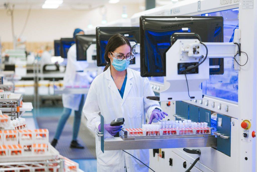 Mayo Clinic Laboratories health care researcher, a white woman wearing glasses and PPE, facemask, gloves while working in the lab with test tubes